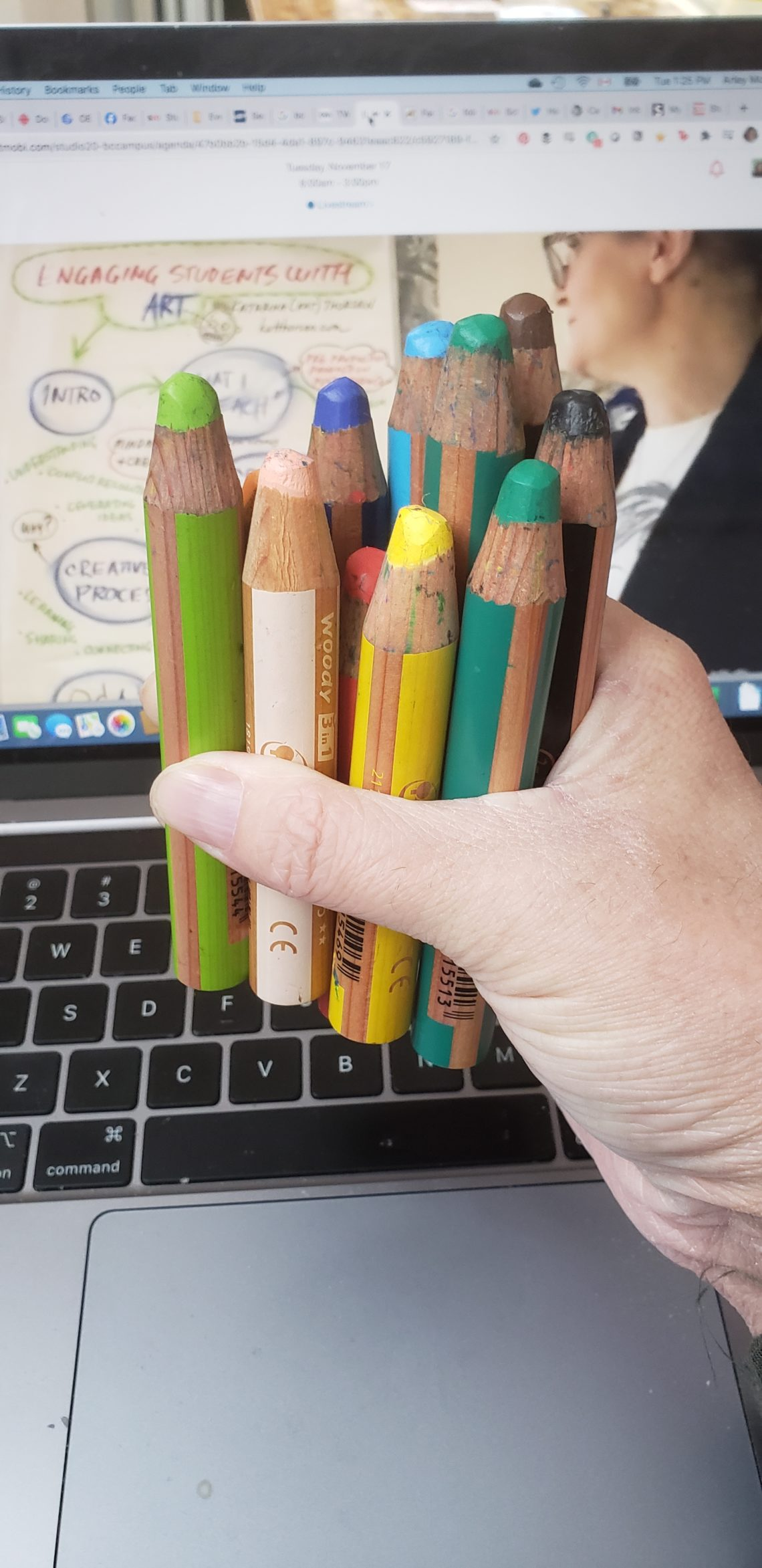 A handful of wooden pencils in Arley's hand in front of a screen